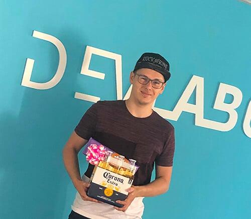 Bild: von Adrian Jakob vor das DevLabor Logo mit ein Geschenk in den Händen